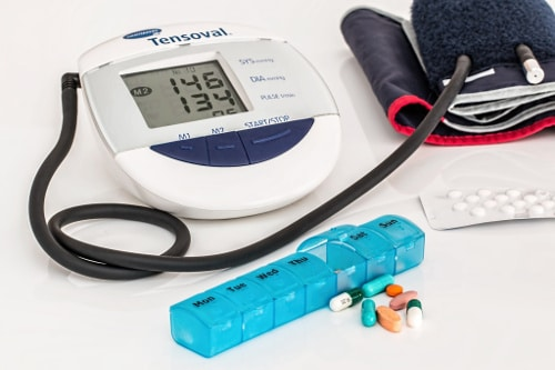 Low testosterone effects (weekly pill container with pills in front, digital blood pressure machine and cuff, pills sealed in aluminum packaging)