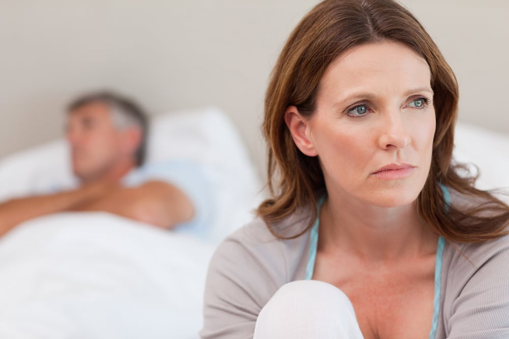 How to decrease testosterone —Sad mature woman on bed with her husband in the background