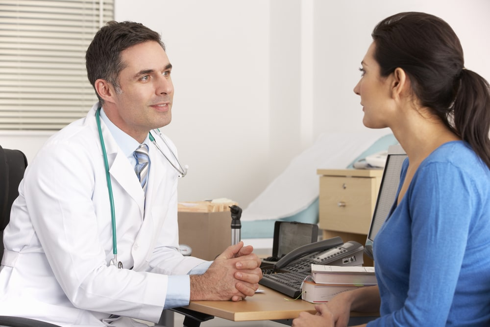 Doctor talking to woman about high progesterone symptoms