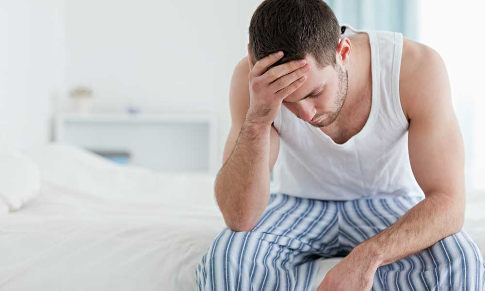 The symptoms of a pituitary tumor — man in PJs holding head with one hand on edge of the bed.