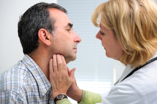 female doctor touching the throat of a patient in the office — thyroid and low testosterone