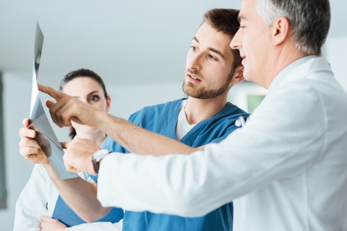 Professional medical team with doctors and surgeon examining patient's x-ray image, possibly discussing the benefits of testosterone replacement therapy.
