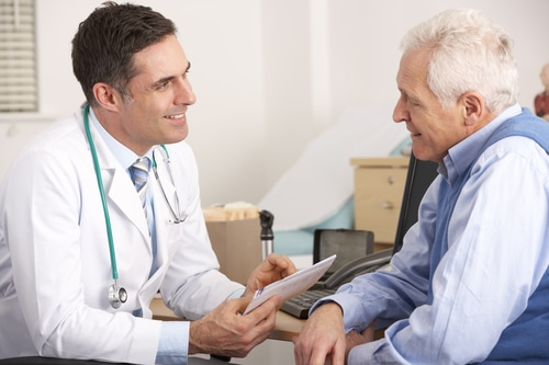 Doctor talking to senior man in an office appointment about chronic low testosterone