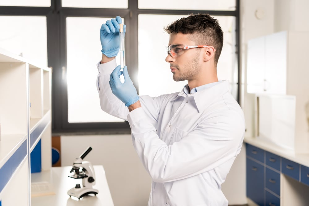 Young male doctor in a laboratory using a microscope conducting a lab experiment, possibly for a Low T test.