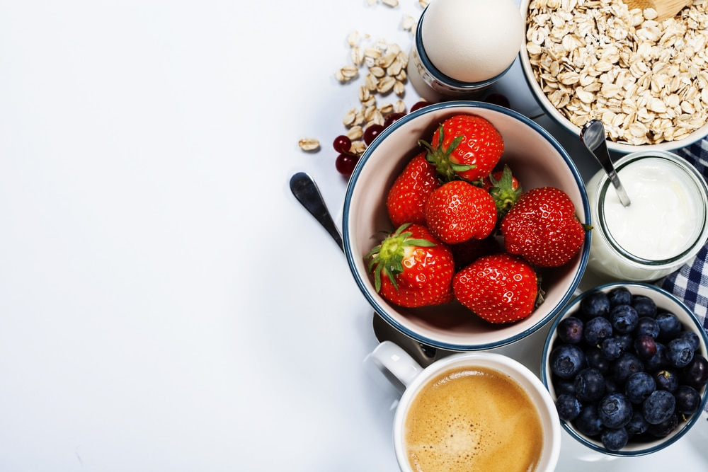 A variety of healthy foods that could help regulate women's hormones, including an egg, strawberries, blueberries, and coffee with milk.