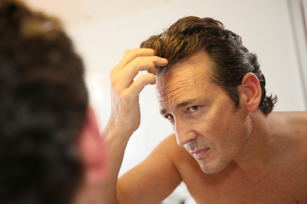 A middle-aged man with no shirt is checking his hairline in the bathroom mirror — he may be concerned about the genetics of male pattern baldness.