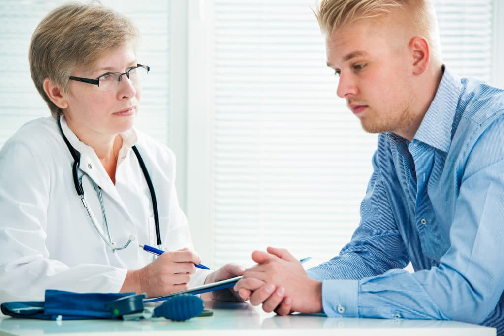 A female doctor wearing a white lab coat and glasses discusses hypothyroidism symptoms with a male patient who has blonde hair and is wearing a blue shirt.