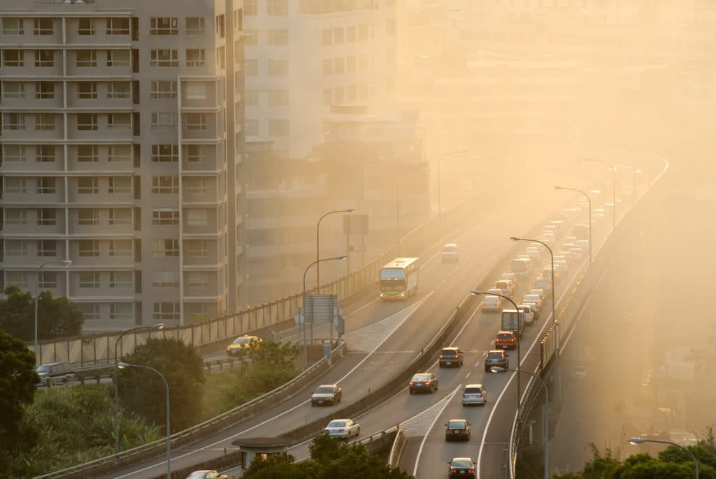 A traffic-congested elevated highway passes near a high-rise apartment building. The air is heavily polluted with yellow smog. Poor air quality in Dallas presents a problem for area residents' health.