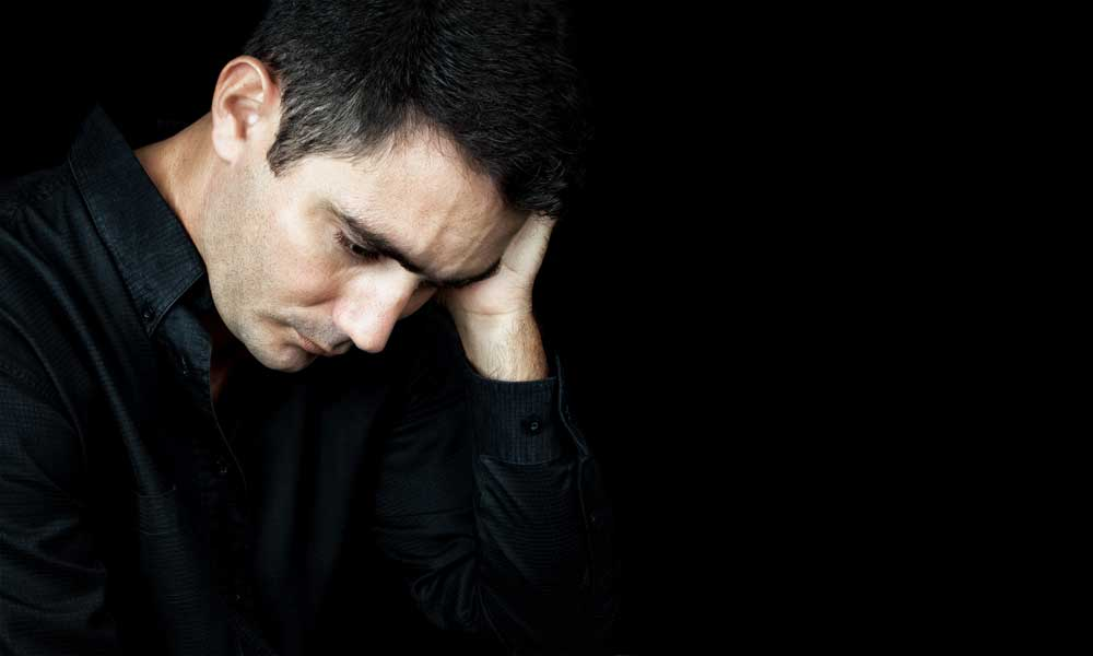A man suffering from depression before beginning Testosterone Replacement Therapy. TRT can help with symptoms like mild anxiety and depression. Learn more.