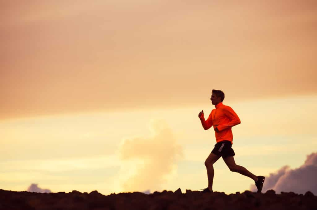 A man in a red jacket and shorts is pictured running against an evening sunset background. He may be preparing for one of the many fitness events in Dallas that will be held in 2018.