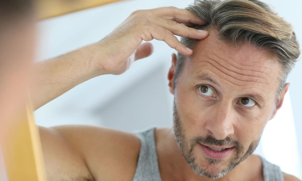 A man checking for hair loss in the mirror. Many men fear that they will lose their hair as a result of TRT, but that's not quite how testosterone and hair loss are related. Learn more.