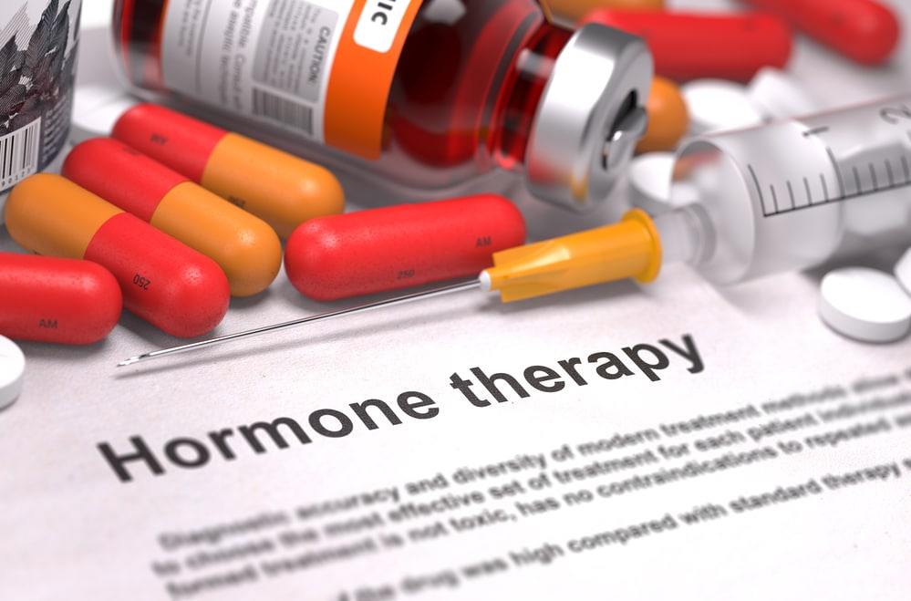 "The words ""hormone therapy"" on a piece of paper surrounded by pills and needles. Hormone therapy, especially testosterone replacement therapy, can be complex and should be handled by a trained medical professional. Learn More."