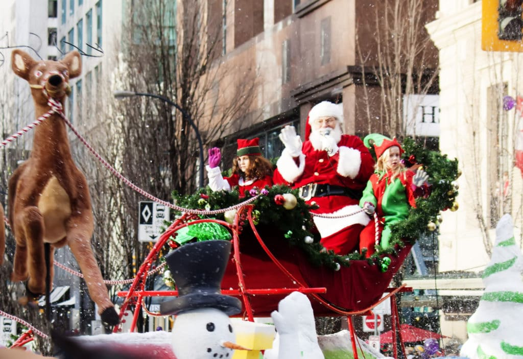 A parade float carrying Santa Clause and a few elves moves down a city street. A snowman waves in the foreground. The Christmas Parade is one of the holiday events happening in Lewisville each year.