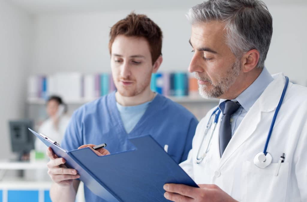 A doctor and physician's assistant look over a patient's test results, possibly from the Low T test at TCT Lewisville.