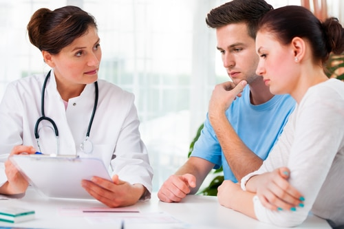 Doctor woman offering medical advices to a young couple in office about fertility. Testosterone Replacement Therapy can reduce or even eliminate male fertility. Learn more.