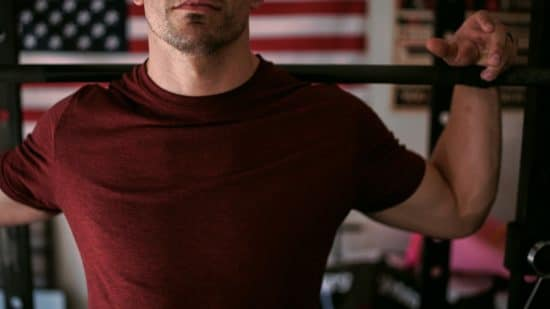 A man lifting weights in his home gym with an American flag in the background. Testosterone Replacement Therapy is not a shortcut for body building, but it can help if you suffer from clinically low testosterone. Learn more.