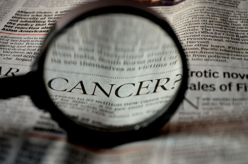 "A magnifying glass over the word ""cancer"" in a newspaper. Testosterone has been in the news once or twice as a possible cause of prostate cancer, but these charges seem to have no basis. Learn more."