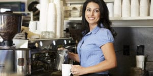 A woman wearing a blue shirt who is working at a coffee shop in Flower Mound draws a cup of coffee from a large coffee machine.