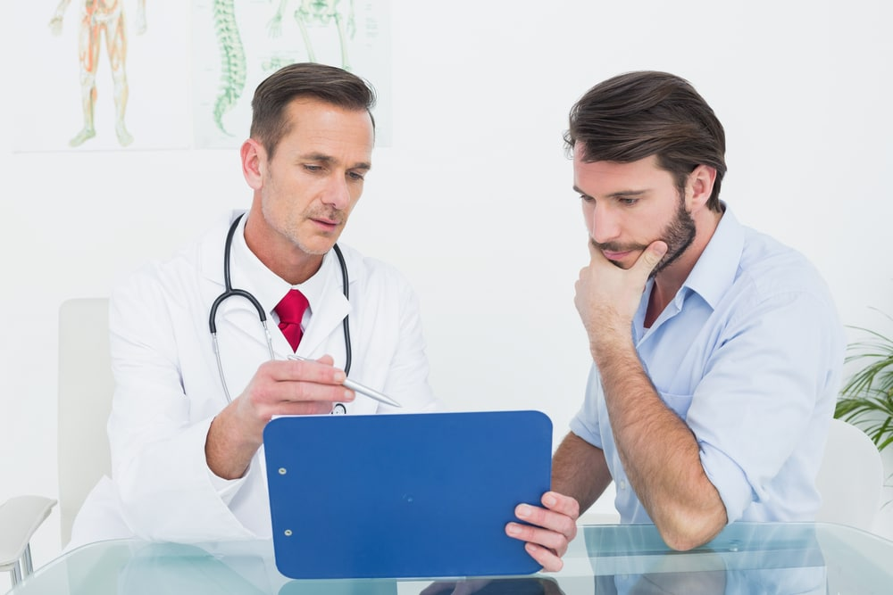 A doctor and a patient sit at a glass table while looking at exam data on a blue clipboard. The doctor gestures with his pen, possibly explaining hypothyroidism treatment available in Dallas- Fort Worth.