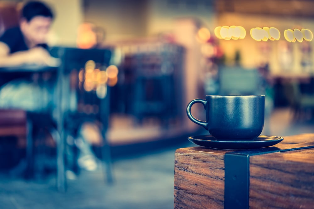 Black coffee mug on a saucer sits on the corner of a rustic wood table in a Prosper cafe.
