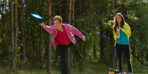 Woman in a pink shirt and black pants throws a disc, while a friend holding a water bottle is watching in the background. The two are possibly joining one of the many Hurst meetups available for people trying to stay active.