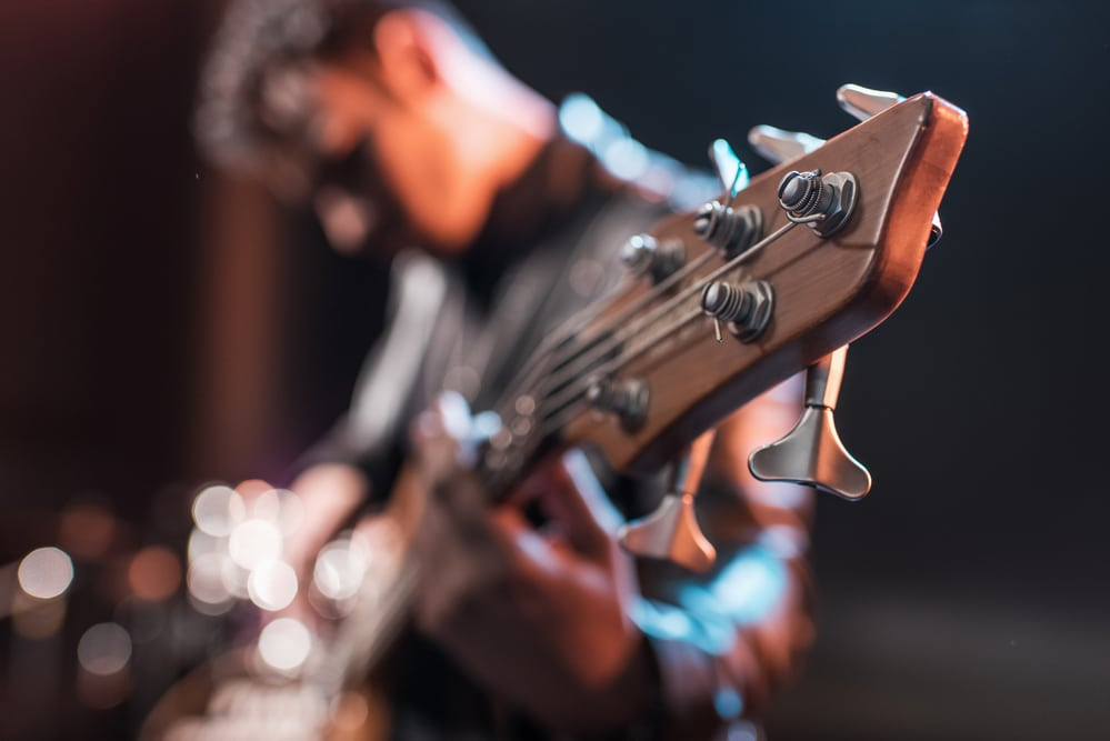 A male guitarist on stage plays a set at a live music venue in Hurst.