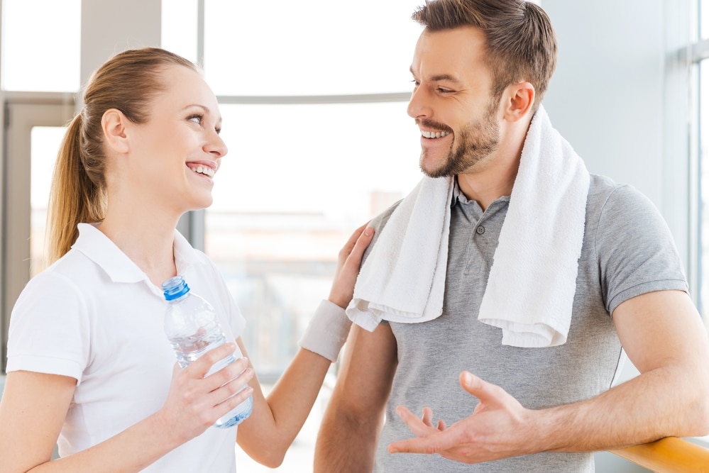 A woman in a white t-shirt talks to a man with short hair, a beard, and a gray t-shirt. The man has a white towel draped around his neck. Both may be members of an employee health initiative in the Dallas-Fort Worth area.