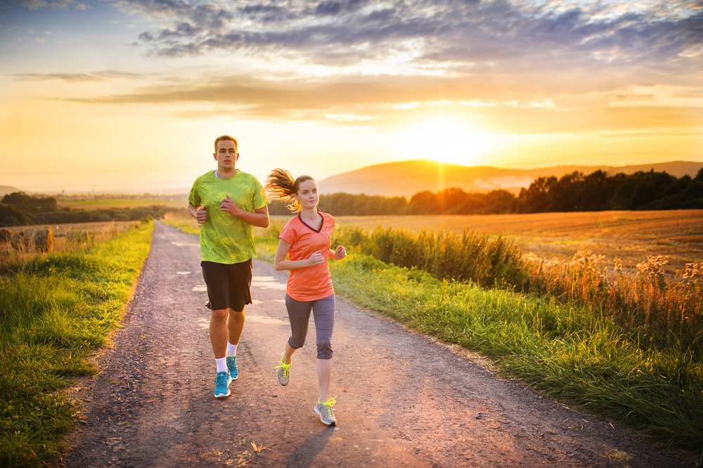 A man and woman wearing workout attire run down a gravel road in a Prosper 5K race with the sun rising in the background.