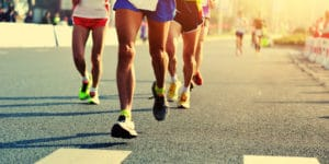 Pictured are the legs of a pack of four runners dressed in running shorts and running shoes, who are running on an asphalt road. The picture is possibly a 5K race in Frisco.