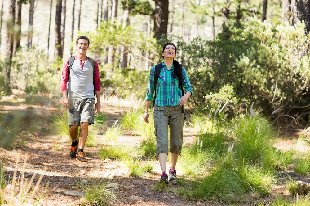 A man and women carrying backpacks are hiking near Lake Lewisville.