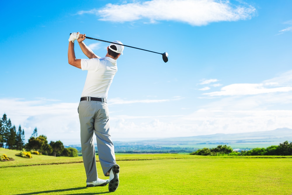 A man in a white shirt and gray slacks tees off on a beautiful golf course against a backdrop of blue skies. Golf is one of many great spring activities you can try in Flower Mound.