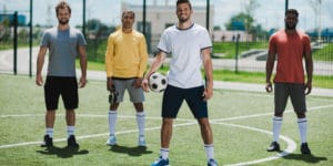 Four men wearing athletic gear are standing on a soccer field. The man in the center is holding a soccer ball on his right hip. The men may be part of one of the many Meetups taking place in Frisco.