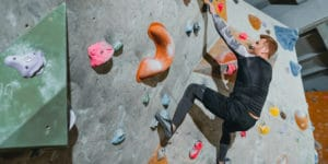 A man with short hair and a beard wearing black athletic gear climbs a colorful artificial climbing wall. Rock climbing has become a popular sport in DFW.