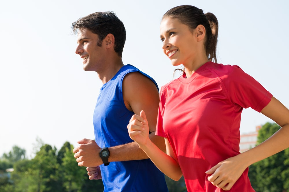 A young couple, a man in a blue tank top and a women in a red t-shirt are running, possibly in a 5k event near Prosper.