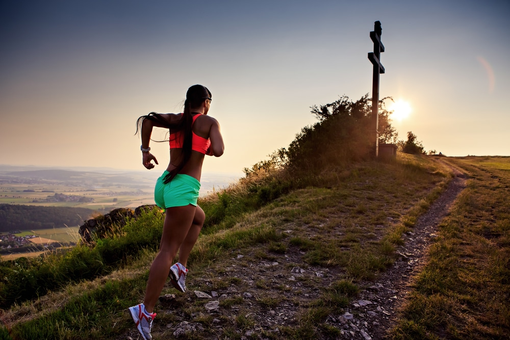 A young woman in athletic attire runs up a mountain trail. Lewisville running events provide opportunities for fun and fitness.