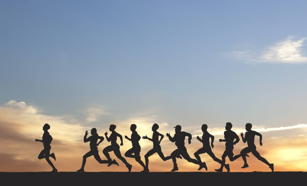 Silhouettes of several runners against a sunset, possibly running a race in Flower Mound.