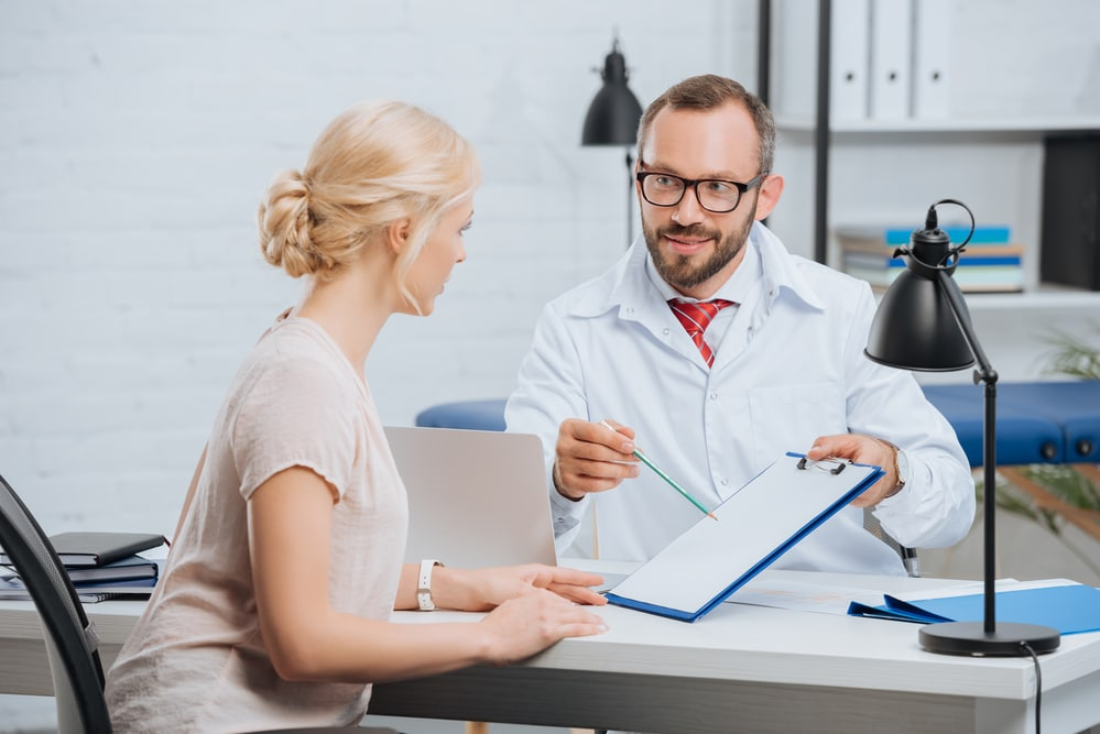 A blonde woman sits at an exam table, having a conversation with a bearded doctor who is showing her a chart on a clipboard. They are possibly discussing testosterone replacement therapy for women.