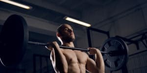 A shirtless man trains in a dark gym, taking advantage of the increased strength gains he experiences from TRT.