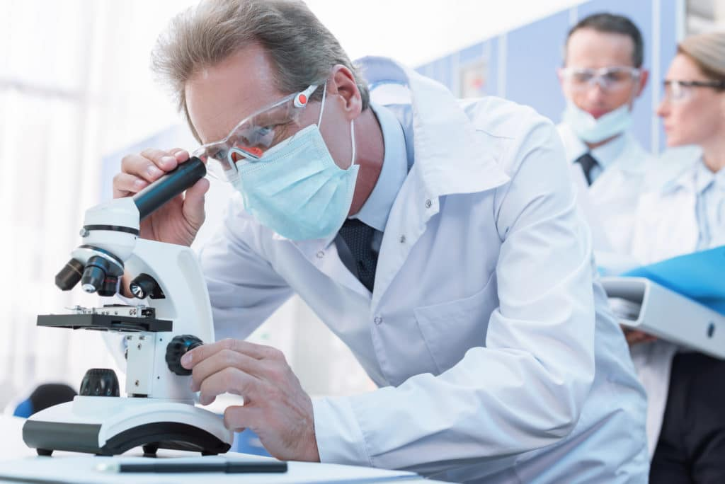 A researcher wearing glasses, mask, and white lab coat looks into a microscope. Scientific research reveals the facts about TRT.