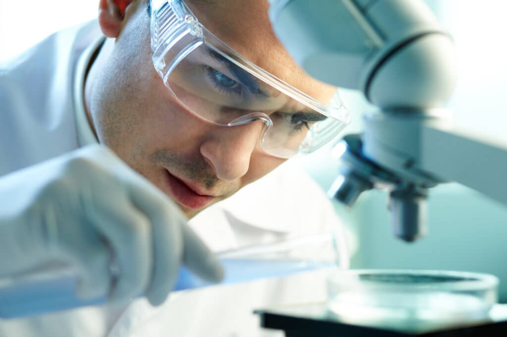A young man wearing protective eye glasses works at a microscope, possibly researching a connection between TRT and cardiovascular disease.