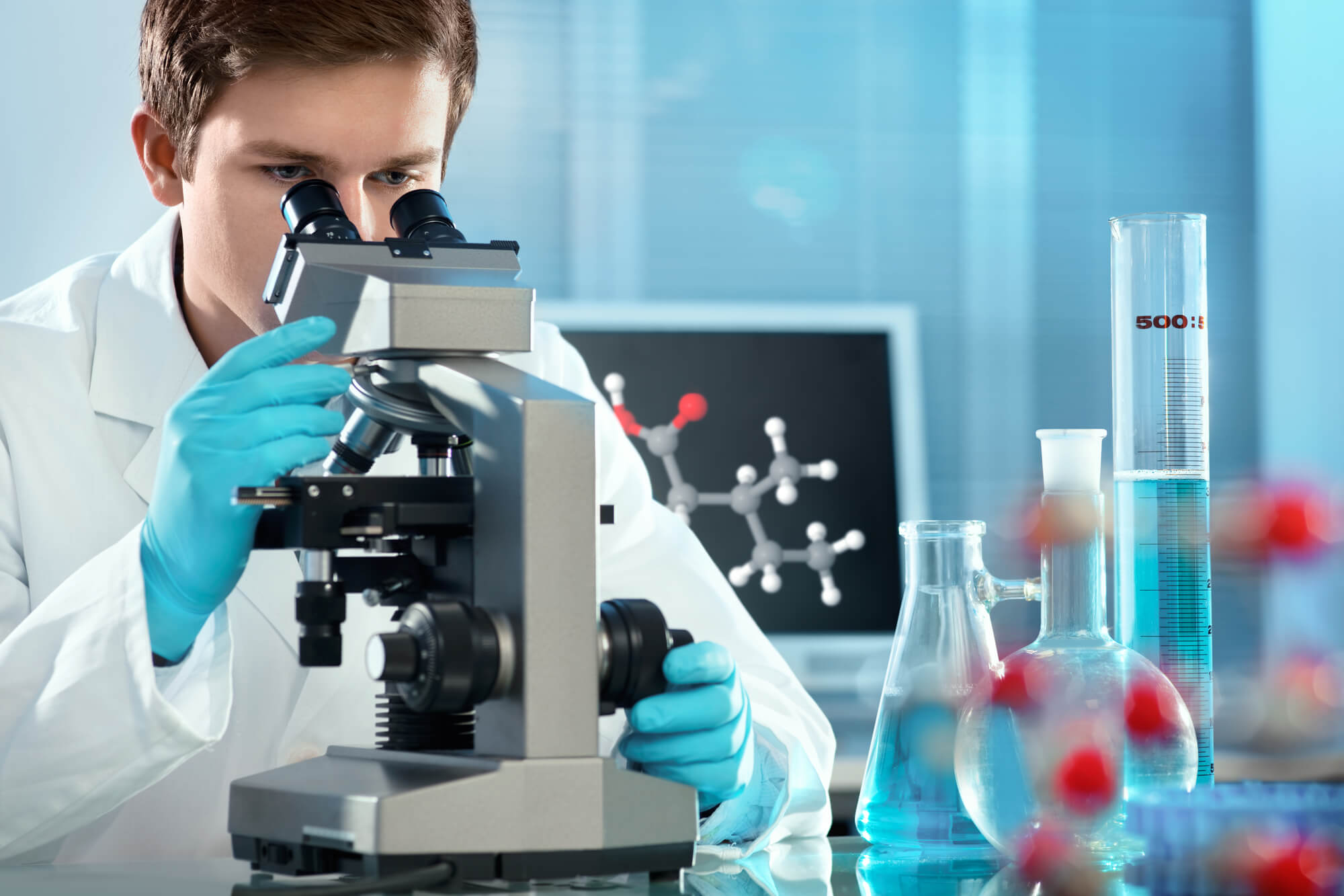 Male researcher looks into a microscope, possibly studying the link between low testosterone and comorbidity.