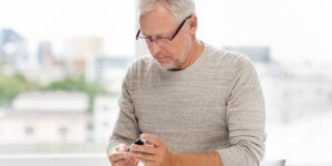 A middle-aged man with short gray hair and glasses tests his blood sugar by pricking his finger. Low testosterone may play a role in the development of type 2 diabetes.