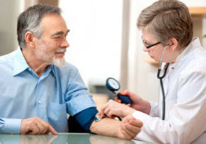 A doctor measures the blood pressure of a male patient. There is no evidence linking TRT to blood clotting events, but preventative monitoring represents best practices.