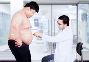A male doctor uses a measuring tape to measure the stomach of an overweight male patient. The potential role of TRT in the prevention of diabetes may be discussed as part of his treatment plan.