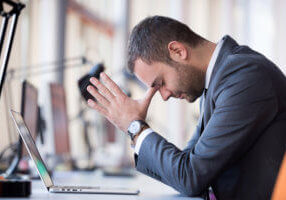 The connection between depression and low testosterone could be what's on the mind of this middle-aged business man, who is wearing a gray suit and sitting in front of a laptop computer with his head resting in his hands.